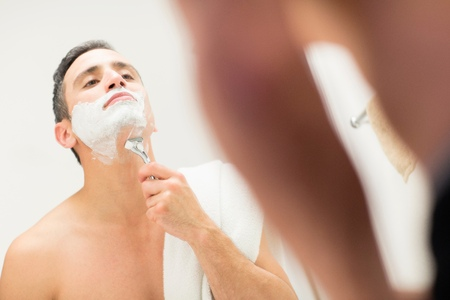 bathroom interior: Mid adult man, looking in mirror, shaving
