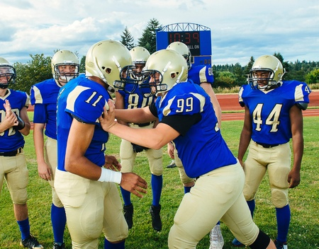 numeric:  American football player pushing teammate on soccer pitch