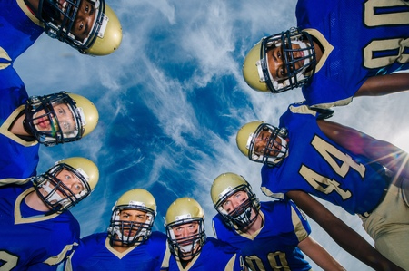 numeric: Low angle portrait of teenage and adult American football team against blue sky LANG_EVOIMAGES