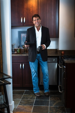 world at your fingertips: Mature man wearing suit jacket and jeans in kitchen, holding digital tablet and coffee mug, looking at camera smiling