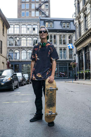 le cap: Young man with skateboard on street, Le Plateau, Montreal, Quebec, Canada