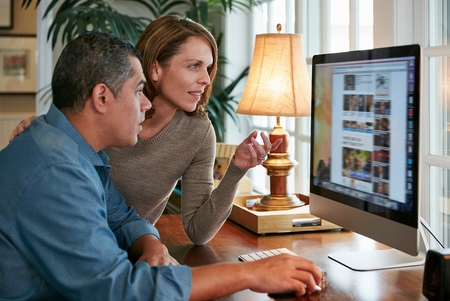 world at your fingertips: Side view of couple at desk using computer