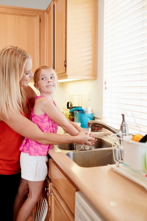 sink: Mother washing daughters hands in kitchen sink LANG_EVOIMAGES