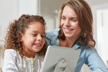 world at your fingertips: Mother and daughter using digital tablet, smiling