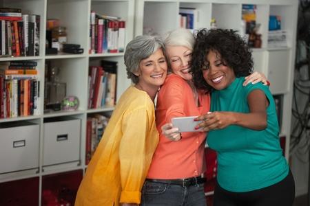 60 64 years: Portrait of three mature women, taking self portrait, using smartphone