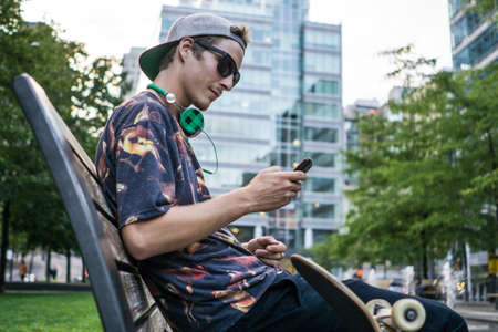 le cap: Young man using smartphone on park bench, Le Plateau, Montreal, Quebec, Canada