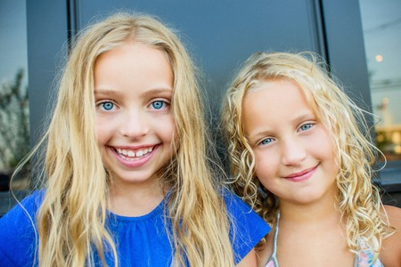 7 8: Portrait of blond haired and blue eyed sisters at sidewalk cafe LANG_EVOIMAGES