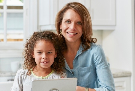 world at your fingertips: Mother and daughter in kitchen with digital tablet looking at camera smiling