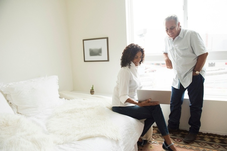 60 64 years: Senior man and wife looking at laptop in bedroom LANG_EVOIMAGES