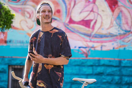 le cap: Young man smiling against graffiti wall, Le Plateau, Montreal, Quebec, Canada LANG_EVOIMAGES