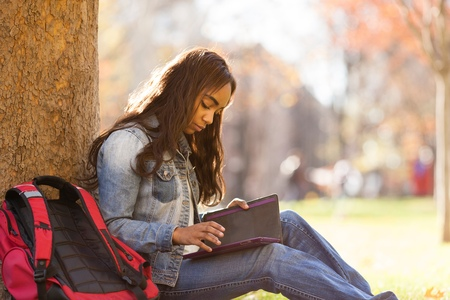 world at your fingertips: Side view of young woman sitting leaning against tree looking down at digital tablet LANG_EVOIMAGES