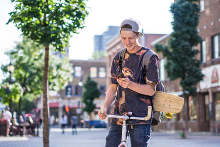 le cap: Young man using smartphone on bicycle, Le Plateau, Montreal, Quebec, Canada