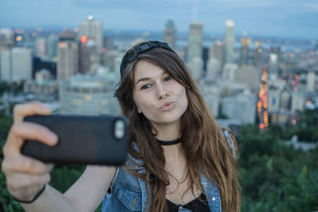 le cap: Young woman taking selfie on hill, Le Plateau, Montreal, Quebec, Canada