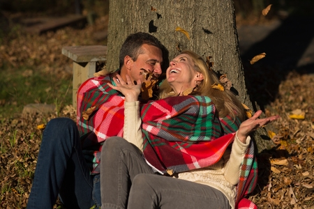 50 54 years: Mature couple sitting against tree trunk throwing autumn leaves at night