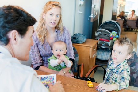 50 54 years: Mother sitting with two children, having discussion with doctor