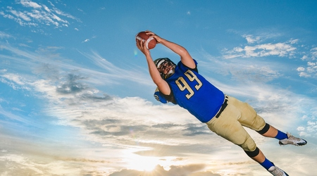 numeric: Male teenage American football player catching ball mid air against blue sky