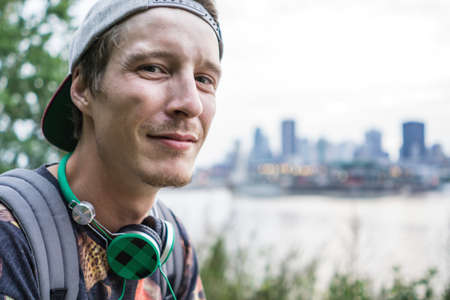 le cap: Young man with headphones by river, Le Plateau, Montreal, Quebec, Canada