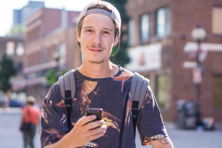 le cap: Young man using smartphone on street, Le Plateau, Montreal, Quebec, Canada