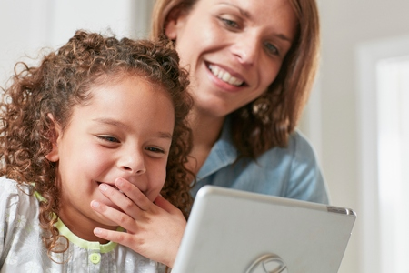 world at your fingertips: Low angle view of mother and daughter using digital tablet, hand over mouth smiling