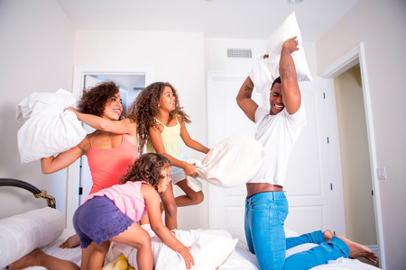 7 8: Family pillow fighting on bed, smiling