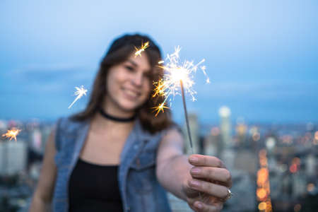 le cap: Young woman playing with sparklers on hill, Le Plateau, Montreal, Quebec, Canada