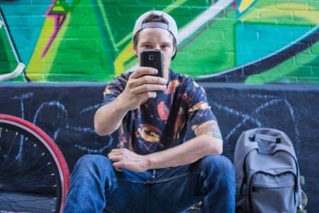 le cap: Young man takng selfie against graffiti wall, Le Plateau, Montreal, Quebec, Canada