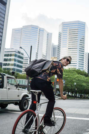 le cap: Young man cycling on street, Le Plateau, Montreal, Quebec, Canada LANG_EVOIMAGES