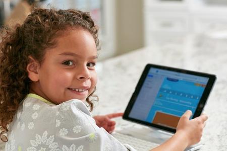 world at your fingertips: Girl using digital tablet looking over shoulder at camera smiling