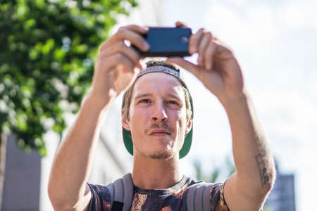 le cap: Young man takng selfie with smartphone, Le Plateau, Montreal, Quebec, Canada
