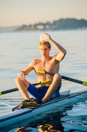 puget sound: Teenage boy in sculling boat, pouring water over head to cool him down