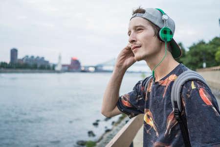 le cap: Young man with earphones using smarpthone on bridge, Le Plateau, Montreal, Quebec, Canada LANG_EVOIMAGES