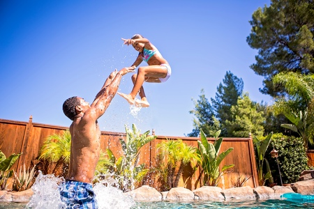 7 8: Side view of father in swimming pool throwing daughter in air smiling