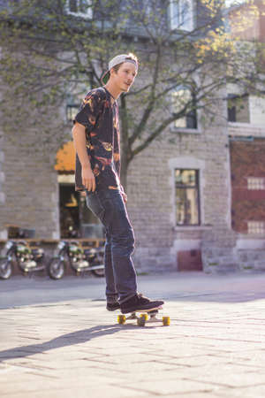 le cap: Young man skateboarding on street, Le Plateau, Montreal, Quebec, Canada