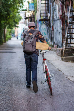 le cap: Young man with skateboard on bicycle in back lane, Le Plateau, Montreal, Quebec, Canada LANG_EVOIMAGES