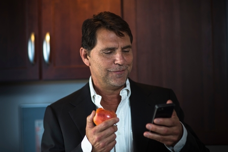 world at your fingertips: Mature man wearing suit jacket holding apple, looking at smartphone smiling LANG_EVOIMAGES