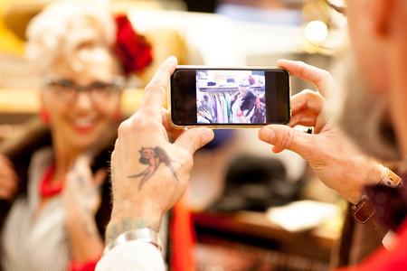english ethnicity: Tattooed hands of senior man taking smartphone photo of girlfriend in antique and vintage emporium