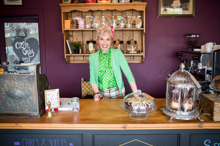 english ethnicity: Portrait of quirky vintage mature woman behind counter in tea rooms