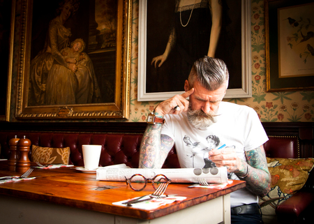 60 64 years: Quirky man doing crossword in bar and restaurant, Bournemouth, England LANG_EVOIMAGES