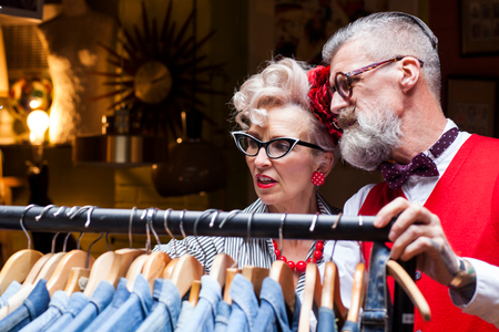 english ethnicity: Quirky vintage couple looking at clothes rail in antiques and vintage emporium