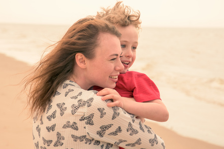 flyaway: Young woman carrying son on beach