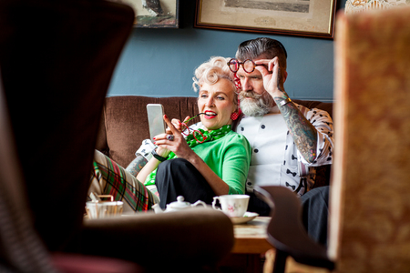 english ethnicity: Quirky vintage couple looking at smartphone in tea room