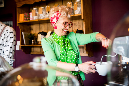 english ethnicity: Quirky vintage mature woman working behind tea room counter