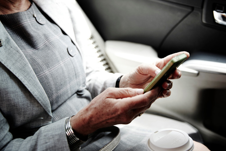 60 64 years: Senior businesswoman sitting in back of taxi, using smartphone, mid section