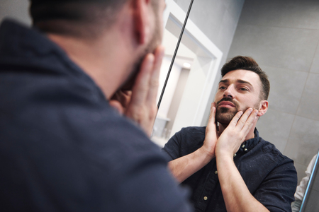 mirror image: Mirror image of bearded man with hands on face LANG_EVOIMAGES