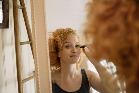 mirror image: Mirror image of woman applying mascara LANG_EVOIMAGES