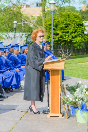 60 64 years: Principle standing at podium, giving speech, on graduation day. Students sitting in rows behind LANG_EVOIMAGES
