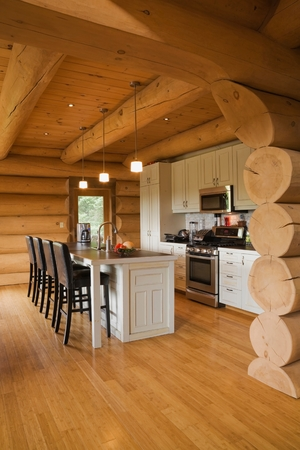 White kitchen cabinets and island and barstools in kitchen of a Scandinavian cottage style log home LANG_EVOIMAGES