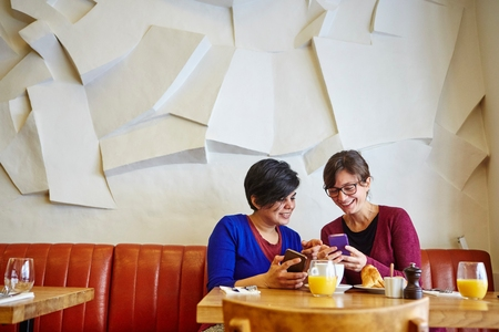 front desk: Two adult female friends reading smartphone text in restaurant