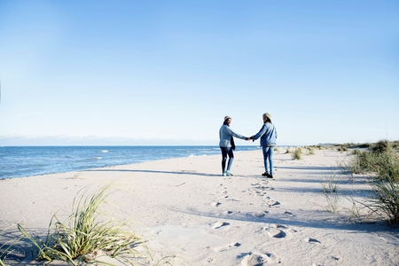 Two young women, walking along beach, holding hands, rear view LANG_EVOIMAGES