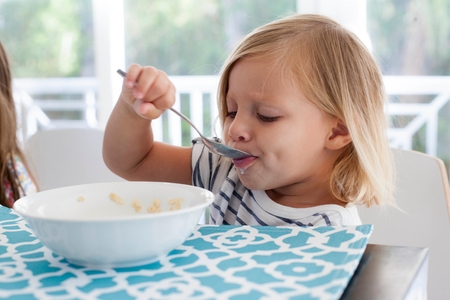 devouring: Girl eating breakfast from bowl with spoon